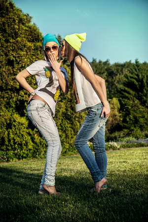 Two young beautiful girls posing outdoor in park, wearing fashionable clothes. Summer photo. Best friends. photo