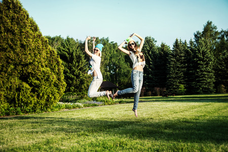 Two young beautiful girls jumping in park, wearing fashionable clothes. Summer photo. Best friends. photo