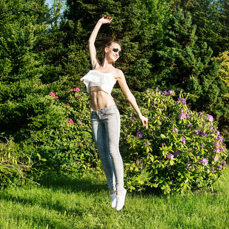 Beautiful young brunette girl jumping over green garden background. Happy woman, summer time. photo