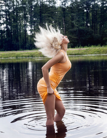 Sexy blonde woman posing in wet dress in lake, summer photo. photo