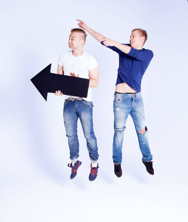 Two young fashionable man posing in studio with black empty arrow, jumping, smiling. Conceptual photo. photo