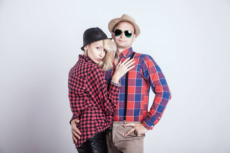 Beautiful blonde young woman posing with handsome man wearing hat, smiling. photo
