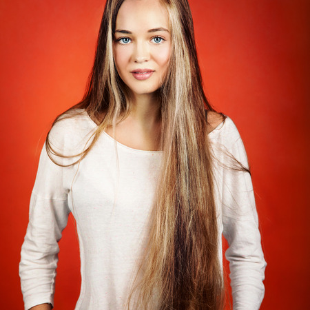 Young beautiful teenage girl with long healthy hair posing over orange background, looking at camera and smiling. photo
