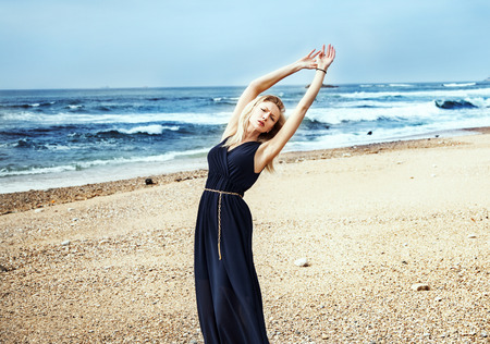 Sensual delicate blonde woman dancing on the beach photo