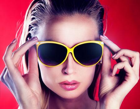 Closeup portrait of beautiful blonde woman wearing fashionable sunglasses. photo