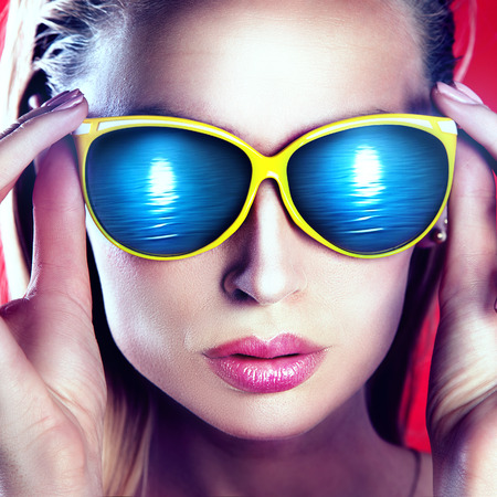 fashionable sunglasses: Closeup portrait of beautiful blonde woman wearing fashionable sunglasses.
