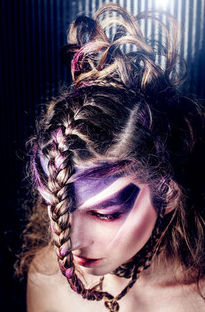 Closeup portrait of beautiful woman with creative modern hairstyle with braids and violet makeup. photo