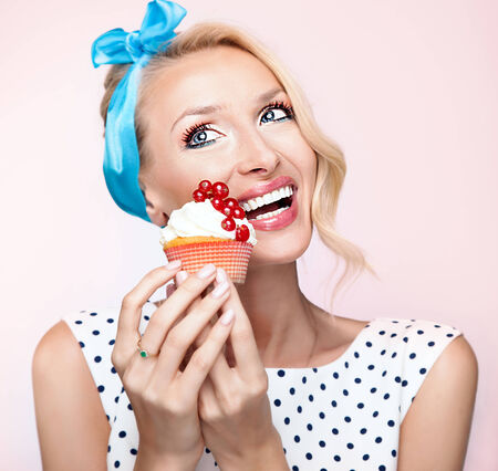 guilty pleasures: Portrait of retro beautiful blonde woman holding sweet cupcake. Girl looking away, smiling, wearing blue ribbon on hair