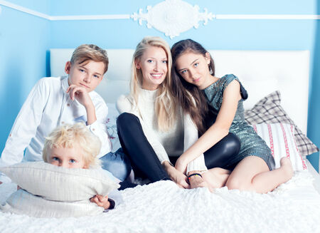 Family time, mother with three children relaxing in bed, looking at camera photo