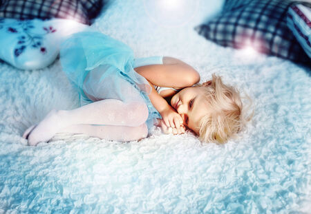 Cute little blonde girl sleeping in big bed, relaxing. Small girl wearing blue princess dress. photo