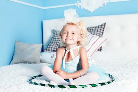 petite fille avec robe: Jolie petite fille blonde assise sur un grand lit, regardant la cam�ra, jouer. Banque d'images