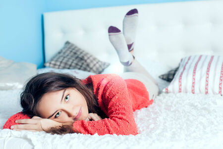 teen girl bedroom: Young teenage girl lying in bed, relaxing, looking at camera