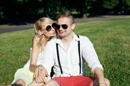 Beautiful young couple on a date in sunny summer day, kissing and smiling photo