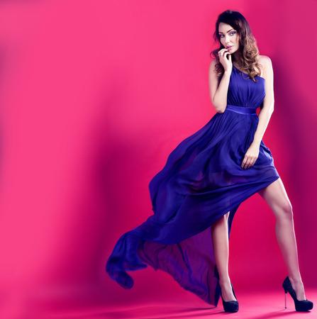 펄럭이는 긴 드레스를 입고 포즈 관능적 인 갈색 머리 아름 다운 여자. 핑크 배경입니다. 소녀는 카메라를보고