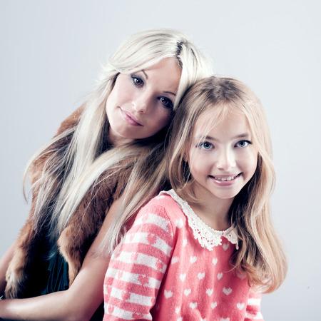 Beautiful mother posing with daughter. Portrait.Studio shot photo