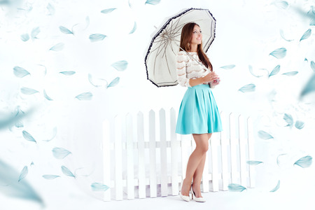 Romantic beautiful brunette woman standing with umbrella. Studio shot.Flying feathers on background photo