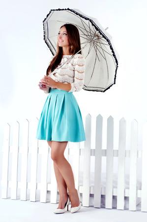Romantic beautiful brunette woman standing with umbrella. Studio shot. photo