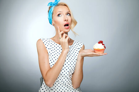 temptative: Portrait of smiling beautiful pinup woman. Girl holding sweet cake. Stock Photo