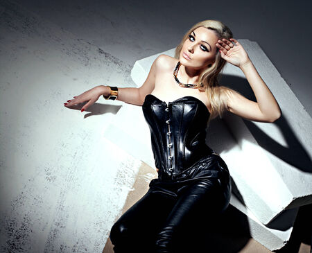 Sexy beautiful blonde woman posing in leather costume, looking at camera. Sensual photo. Banco de Imagens