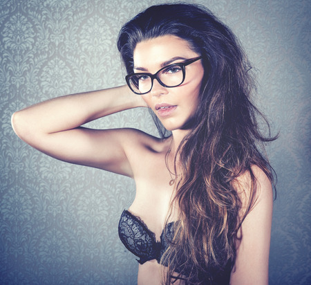 Portrait of attractive woman wearing lingerie and glasses. Stock Photo