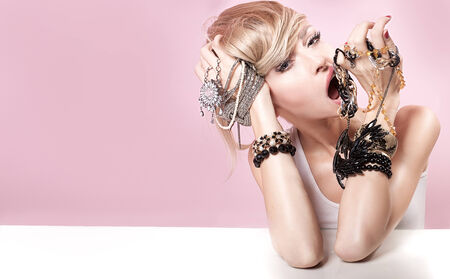 Beauty portrait of attractive delicate blonde woman with jewelry on hands. Girl looking at camera. Pink background. photo
