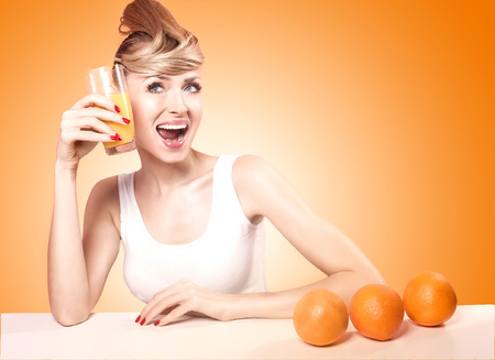 Beautiful young happy woman drinking orange juice, smiling. Healthy lifestyle. photo