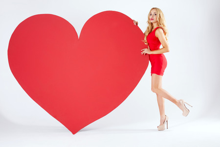 Beautiful sexy blonde woman posing with big red heart. St. Valentines Day. Studio shot. photo