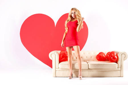 Sexy blonde woman in red dress posing with big heart. St. Valentines day. Studio shot. photo
