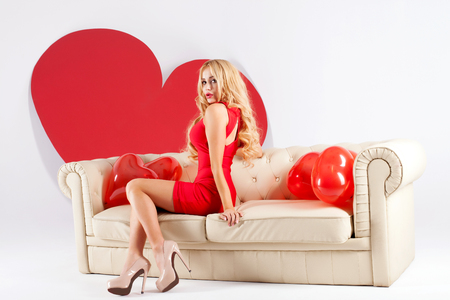 Sensual blonde woman posing over red hearts. Valentines day. photo