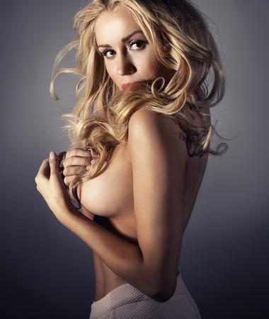 Schönheitsportrait der zarte blonde Frau mit dem langen lockigen Haar. Mädchen nackt, Blick in die Kamera.