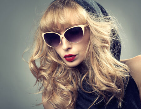 Beauty portrait of delicate blonde woman with long curly hair. Girl wearing fashionable sunglasses. photo