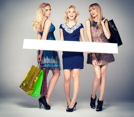 Smiling three beautiful blonde girls shopping, posing with empty boards. Studio shot. photo