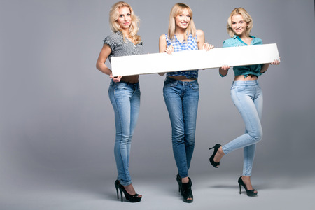 Three beautiful young woman posing in fashionable jeans, holding empty board. Blonde girls. Studio photo. Stock Photo