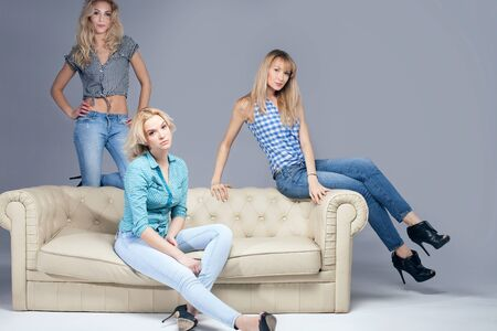 Three beautiful young woman posing in fashionable jeans, looking at camera. Blonde girls. Studio photo.