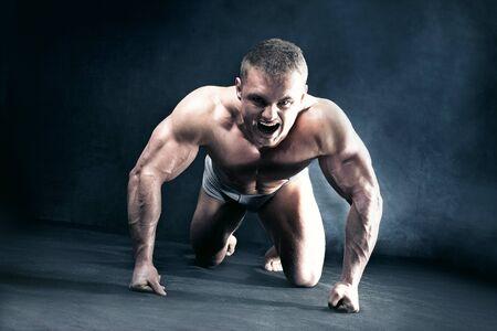 man kneeling: Angry muscular man kneeling, shouting.