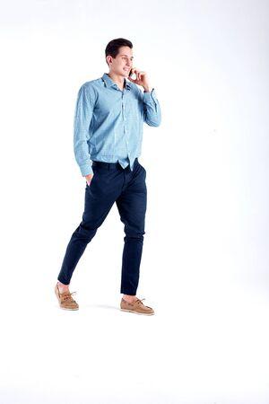 personas caminando: Hombre hermoso joven que habla por el tel�fono. Foto del estudio. Fondo blanco.