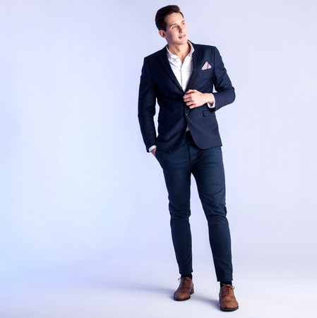 Young handsome man posing in studio wearing fashionable suit. Фото со стока