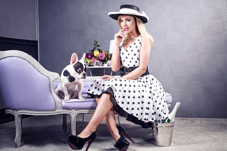 Elegant attractive blonde woman posing in hat and fashionable pinup dress with pug dog.