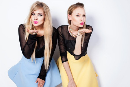 Lovely beautiful blonde girls posing in studio, sending kisses, looking at camera. Fashionable friends.