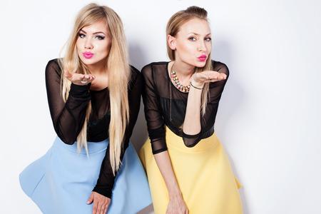 modern girls: Lovely beautiful blonde girls posing in studio, sending kisses, looking at camera. Fashionable friends.