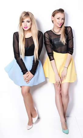 Fashionable young beautiful two woman posing in studio, smiling. Stock Photo
