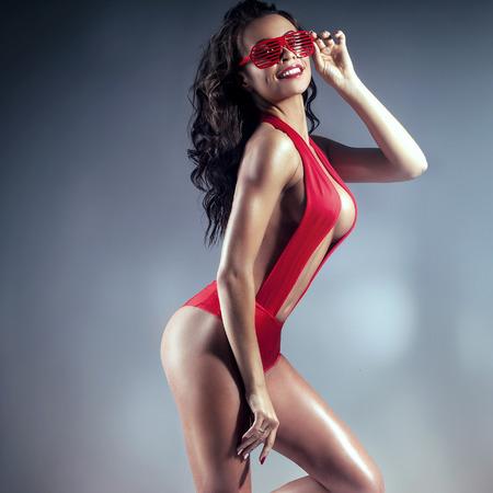 mujer sexy desnuda: Sexy mujer morena posando en ropa interior roja. Estudio de disparo. Señora atractiva con un cuerpo perfecto.