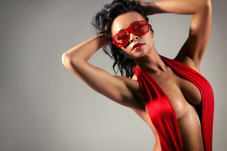 Portrait of sexy brunette woman in red swimsuit and fashionable sunglasses.