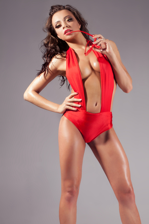nude female body model: Sensual brunette woman posing in studio wearing red sexy beachwear and  sunglasses. Girl with long curly hair.