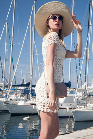 Elegant beautiful blonde lady posing over boats. Summer photo. Attractive smiling woman in fashionable dress and sunglasses. Blue sky. Outdoor photo. photo