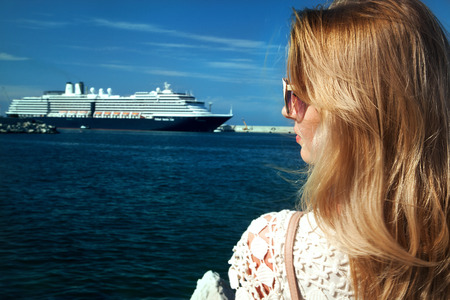 Portrait of beautiful blonde woman looking at passenger ship. Summer photo. photo