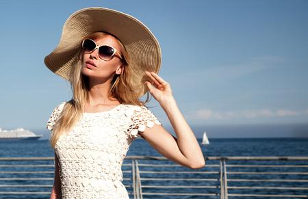 anteojos de sol: Mujer rubia hermosa que presenta en el día soleado de verano. Chica con gafas de sol y sombrero de moda.