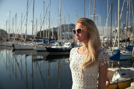 Beautiful blonde woman posing in harbor at sunny summer day. Girl wearing fashionable sunglasses . photo
