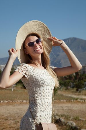 Smiling blonde attractive woman posing in sunglasses and hat. Village on background. photo