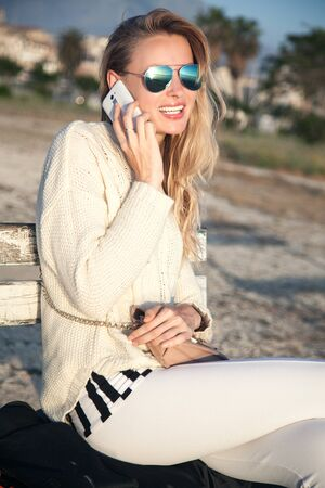 Young beautiful girl talking by mobile phone. Outdoor photo. Sunny day. photo